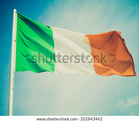 Vintage retro looking Irish flag over a blue sky background