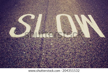Vintage retro looking Slow warning sign painted on a street - stock photo