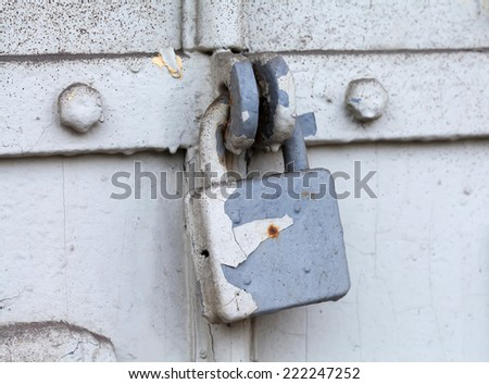 Vintage (retro) metal lock on a gray door. Classic hanging lock. Attrition, old paint and dirt. Soft focus. - stock photo