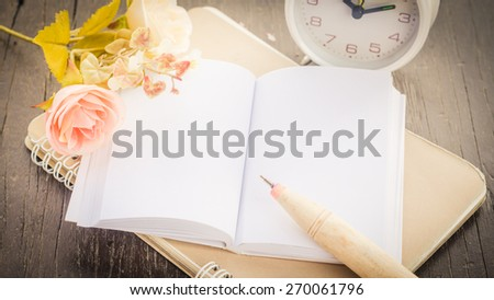 Vintage,retro of note book paper and pen on wooden background soft focus. - stock photo