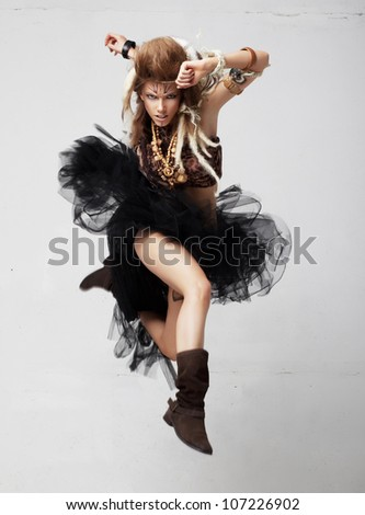 Vintage. Retro style. Excited native female jumping in joy. Antique tribal clothing. Painted face with tattoo - stock photo