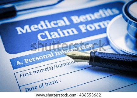 Vintage / retro style : Fountain pen, a chest-piece of a stethoscope and a medical benefits claim form on a clipboard. A blank / empty form is waiting to be completed and signed by an insured person. - stock photo