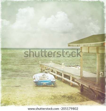 Vintage retro stylized photo of Caribbean beach, seascape with boats and clouds in the background   - stock photo