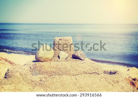Vintage retro toned simple sandcastle on a beach, summer holidays concept. - stock photo
