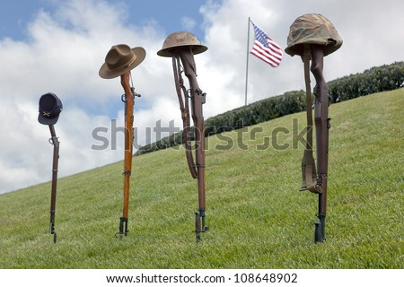 Vintage rifles and soldier's hats and helmets forming Fallen Soldier Battle Crosses, American Flag behind, left to right, eras of Civil War, Spanish American War, WWI, and WWII. - stock photo