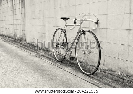 Vintage road bicycle leaning on white wall
