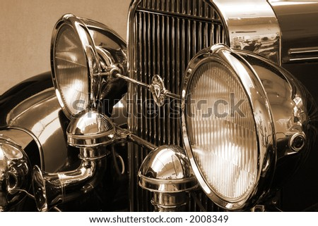 vintage roadster headlights and grill in sepia tone - stock photo