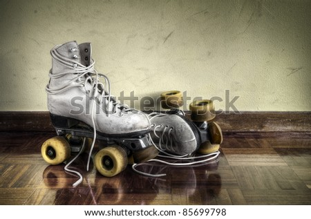 Vintage roller skates with big shoe-laces on a yellow wall background - stock photo
