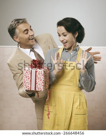 Vintage romantic couple at home, he is giving to his wife a beautiful surprise gift - stock photo