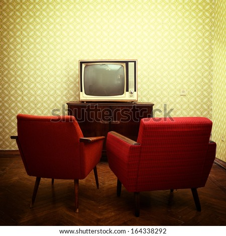 Vintage room with two old fashioned armchairs and retro tv over obsolete wallpaper. Toned - stock photo
