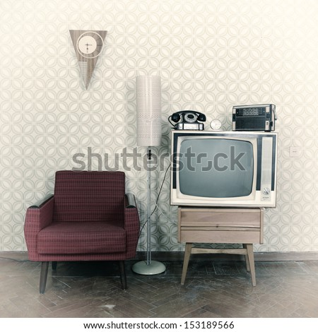 Vintage room with wallpaper, old fashioned armchair, retro tv, phone, clocks, radio player and standart lamp. Image toned, noise added and vignetted - stock photo