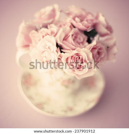 Vintage roses in a cup - stock photo