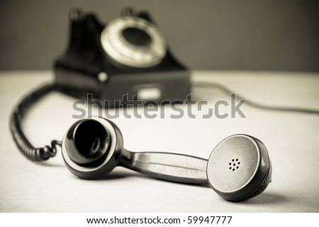 Vintage Rotary Dial Telephone. Old newspaper photo style. Soft focus with focus on handset. - stock photo
