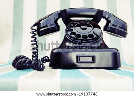 Vintage rotary phone on stripy background - stock photo
