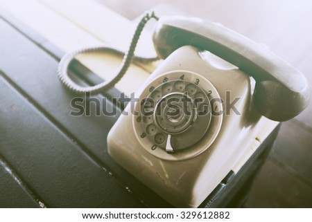 vintage rotary telephone on wood table background - stock photo