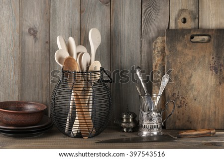 Vintage rustic kitchen still life: silver glass holder with cutlery, ceramic dishware, wire basket with wood spoons and cutting boards against vintage wooden background. - stock photo