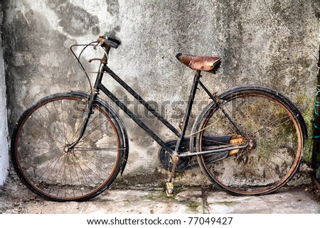 vintage rusty bicycle against a concrete wall