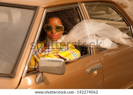Vintage 70s fashion afro woman with sunglasses driving in brown seventies car.