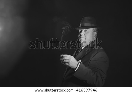 Vintage 1930s gangster holding cigar. Classic black and white portrait.