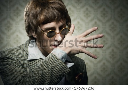 Vintage 1960s style guy after snorting cocaine cleaning his face. - stock photo