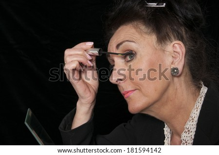 Vintage 1940's style woman applying her make up isolated on black background
