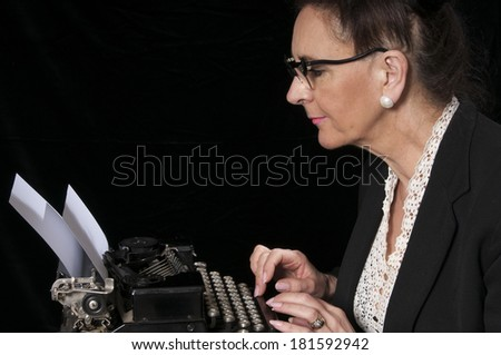 Vintage 1940's style woman in office situation, struggling with her typewriter, isolated on black background - stock photo