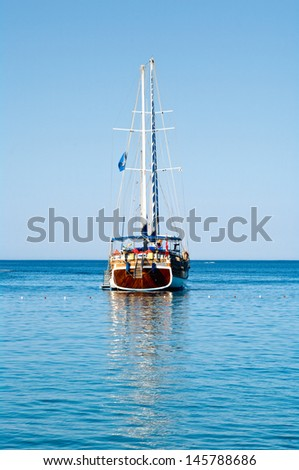 Vintage sailing boat anchored in lagoon of the Mediterranean Sea - stock photo