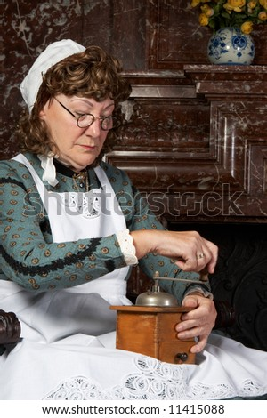 """Vintage scene of a victorian woman working with a coffee grinder. Shot in the antique castle """"Den Brandt"""" in Antwerp, Belgium (with signed property release for the Castle interiors). - stock photo"""