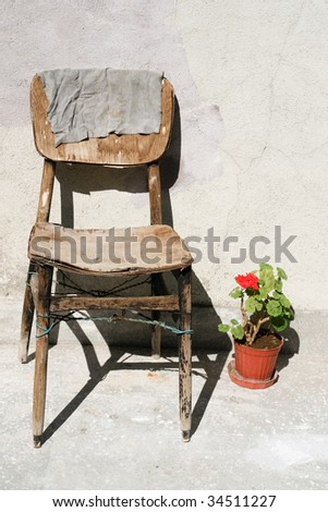 vintage scene with very old chair and flower pot - stock photo