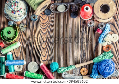 Vintage scissors, needle and threads on tailor table - stock photo