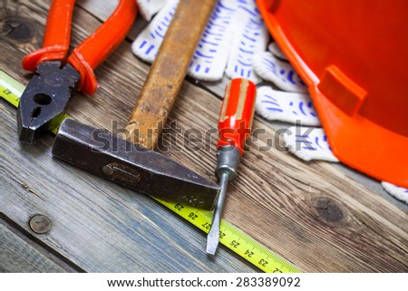 Vintage screwdriver, old hammer, pliers, construction helmet, protective gloves and a measuring tape on ancient boards - stock photo