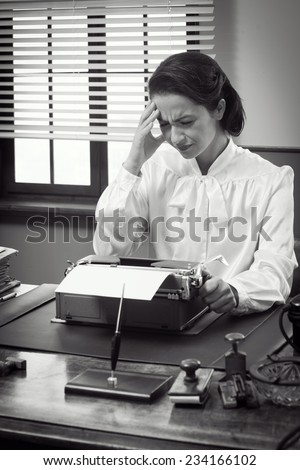 Vintage secretary with headache working at office desk touching her temples