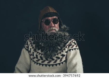 Vintage senior man with knitted sweater, fur collar and sunglasses - stock photo