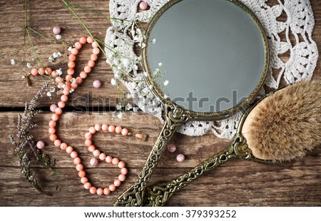 Vintage set - hand mirror with a hairbrush with natural bristles and a necklace of white coral on the old wooden table. - stock photo