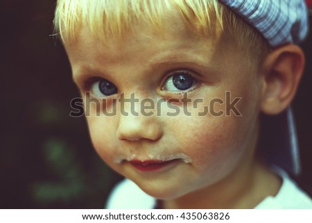 Vintage. Shallow depth of field, motion blur, blur.  Happy kid with ice cream remains on the lips slyly looks at you.  Summer time. - stock photo