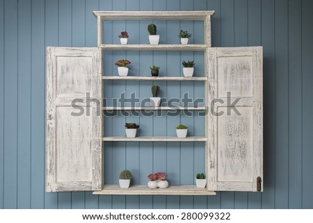 vintage shelf with little cactus plants in pots on wall - stock photo