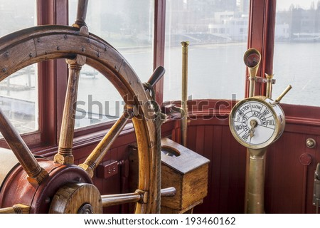 vintage ship bridge with steering wheel and engine controls (telegraph)