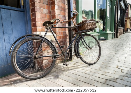 Vintage shop bicycle with wicker basket on the front, leaning against a shop wall padlocked and chained.  Shot close up from low eye level. - stock photo