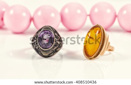 Vintage silver ring with a large amethyst and gold ring with amber on a background of pink beads with large beads - stock photo
