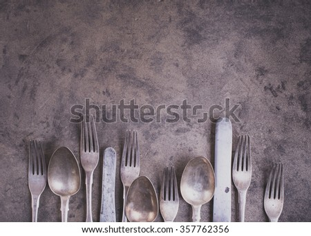 Vintage silverware from bottom side of grunge background top view matte color - stock photo