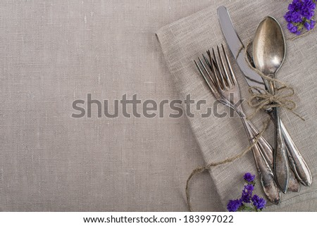 Vintage silverware with flowers and paper rope - stock photo
