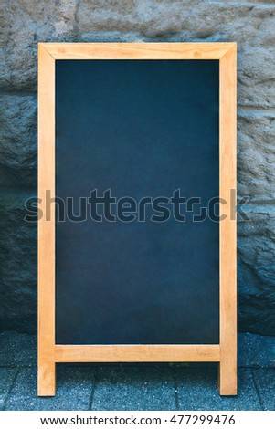 Vintage slate chalk board with wooden frame on stone background