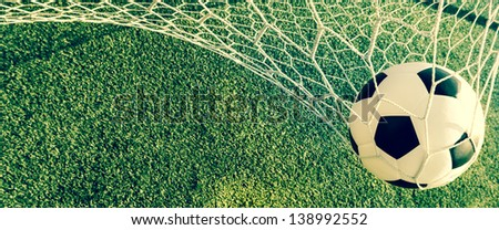 Vintage soccer ball in net, goal scroll, background - stock photo