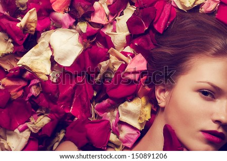 Vintage spa concept. Portrait of a fashionable red-haired (ginger) model with sexy pink lips lying on fading rose petals background. Retro style. Close up. Copy-space. Studio shot