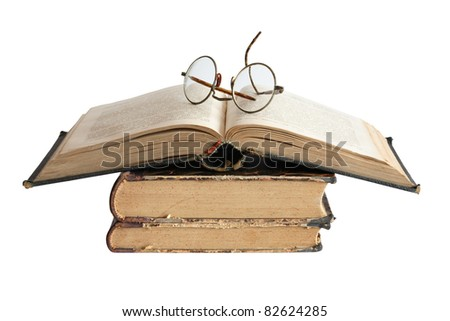 Vintage spectacles lying on old books. Isolated on white background with clipping path - stock photo