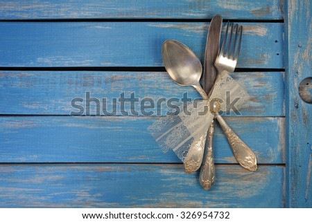 Vintage spoon, fork and knife decorated with lace bow knot on rustic wooden background - stock photo