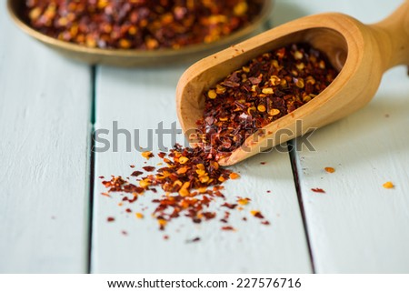 Vintage spoon with crushed red chili on white contrast table - stock photo