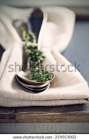 Vintage spoons and thyme sprig on a napkin retro toned selective focus - stock photo