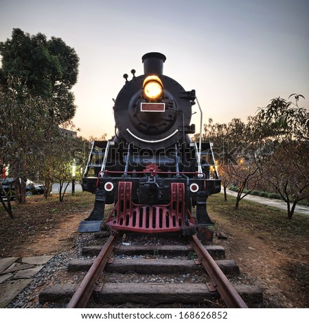 Vintage Steam Engine train with sunset - stock photo