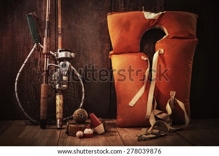 Vintage still life fishing poles and life jacket - stock photo